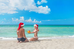 Woman in santa hat  giving a present to her boyfriand on the sea Royalty Free Stock Images