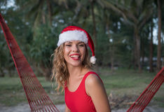 Woman in santa hat on hammock at the beach Stock Image