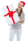 Woman in Santa hat holding big Christmas present Royalty Free Stock Photos