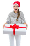 Woman in Santa hat holding big Christmas present Stock Photo