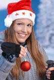 Woman in santa hat holding christmas decoration Royalty Free Stock Images