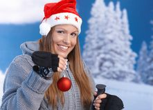 Woman in santa hat holding christmas decoration Stock Photos