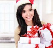 Woman in Santa hat holding Christmas gifts Royalty Free Stock Photo
