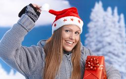 Woman in santa hat holding christmas present Stock Images