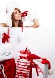 Woman in santa hat holding empty board Stock Photos