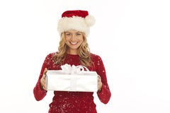 Woman in Santa hat holding gift Stock Photo