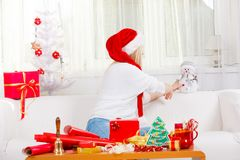 Woman in Santa hat holding gift, snowman decoration. Christmas gifts and presents concept. Blonde woman in Santa Claus hat sitting on couch, holding gift Stock Photo