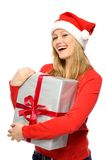 Woman in Santa hat holding gifts Stock Photo