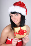Woman in santa hat holding golden present Stock Images