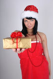 Woman in santa hat holding golden present Royalty Free Stock Image