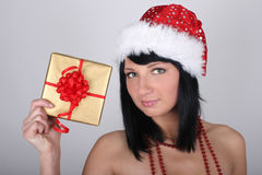 Woman in santa hat holding golden present Royalty Free Stock Photo