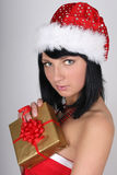 Woman in santa hat holding golden present Royalty Free Stock Photos