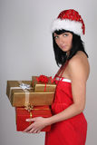 Woman in santa hat holding golden and red pre Royalty Free Stock Photo