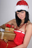 Woman in santa hat holding golden and red pre Stock Photo