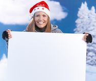 Woman in santa hat holding huge letter smiling Royalty Free Stock Photo
