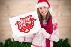Woman in santa hat holding a merry christmas placard Royalty Free Stock Photography