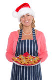 Woman in Santa hat holding a plate of gingerbread men stock photo