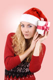 Woman in Santa hat holding present Stock Image