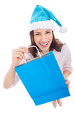 Woman in Santa hat holding shopping bag Stock Photos