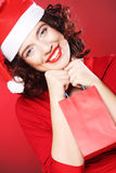 Woman with Santa hat holding shopping bag, Stock Photography
