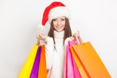 Woman in santa hat holding shopping bags Royalty Free Stock Photography