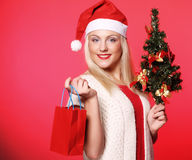 Woman with Santa hat holding shopping bags Royalty Free Stock Image