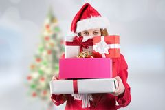 Woman in santa hat holding stack of gifts Royalty Free Stock Images