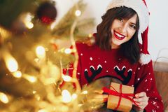 Woman in santa hat holding stylish gift under christmas tree wit. H garland lights and golden ornaments. space for text. seasonal greetings, happy holidays Royalty Free Stock Photos