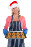 Woman in Santa hat holding a tray of gingerbread men stock photo