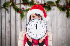 Woman in santa hat holding a wall clock against digitally generated background Royalty Free Stock Photo