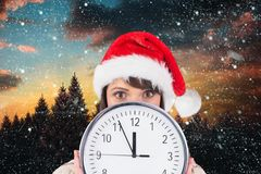Woman in santa hat holding a wall clock against digitally generated background Stock Images