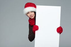 Woman in Santa hat holding white banner Royalty Free Stock Image