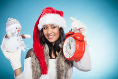 Woman in santa hat with little snowman and clock. Royalty Free Stock Photography