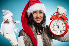 Woman in santa hat with little snowman and clock. Royalty Free Stock Image