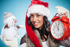 Woman in santa hat with little snowman and clock. Royalty Free Stock Photo