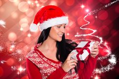Woman in santa hat looking at christmas gift against digitally generated background Stock Photos