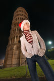 Woman in Santa hat looking on something near Leaning Tower, Pisa Stock Photography