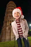 Woman in Santa hat looking up near Leaning Tower of Pisa Royalty Free Stock Images