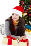Woman in Santa hat lying under Christmas tree. Smiling woman in Santa hat lying under Christmas tree over white Royalty Free Stock Photo