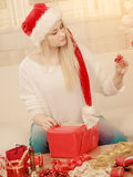 Woman in Santa hat opening christmas gifts Stock Photos
