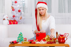 Woman in Santa hat opening christmas gifts Royalty Free Stock Images