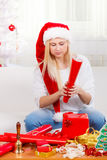 Woman in Santa hat packing christmas gifts Stock Photos