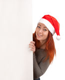 Woman in santa hat peeking out of blank poster Royalty Free Stock Photos