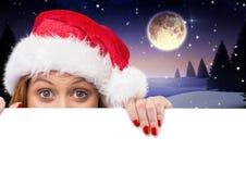 Woman in santa hat peeking over white card Stock Photo