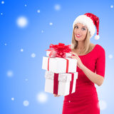 Woman in santa hat posing with gift boxes over christmas backgro Royalty Free Stock Images