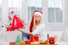 Woman in Santa hat preparing christmas gifts Royalty Free Stock Photo