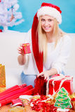 Woman in Santa hat preparing christmas gifts. Holiday gifts, seasonal concept. Woman in Santa hat sitting on sofa preparing and packing christmas presents Royalty Free Stock Photography