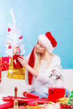 Woman in Santa hat preparing christmas gifts Stock Images