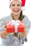 Woman in Santa hat presenting Christmas gift box Royalty Free Stock Photography