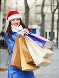 Woman in Santa hat with purchases Royalty Free Stock Images